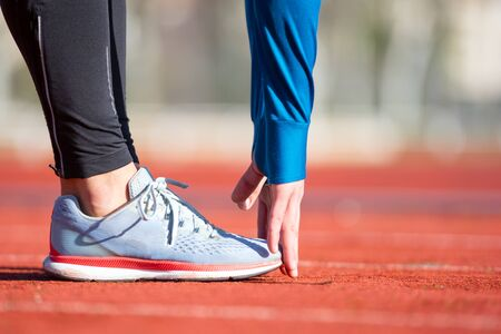 Close up view, athlete stretching on a running track. Фото со стока