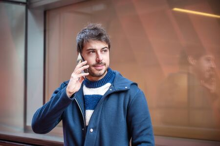 Portrait of handsome young man talking on mobile phone on the street, of modern city center. People and technology.