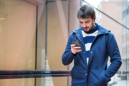 Handsome young man, standing outside the office building, using social networks on mobile phone while having a break at work.