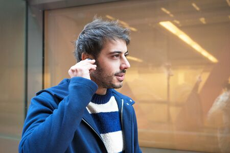 Handsome young man, putting on wireless earphones while walking, urban city background.