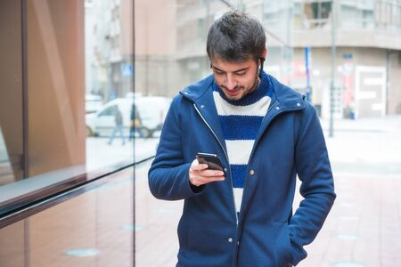 Handsome young man, standing outside the office building, using mobile phone while having a break at work.