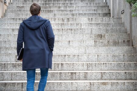Young man Holding Computer Laptop Walking Up Stairs outdoor.