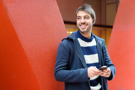 Happy man using a smart phone standing in the street. Red color modern office buildings in the background.
