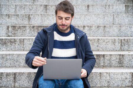 Hübscher Hipster moderner Geschäftsmann, Laptop in der Stadt verwendend, mit positivem Ausdruck. Standard-Bild