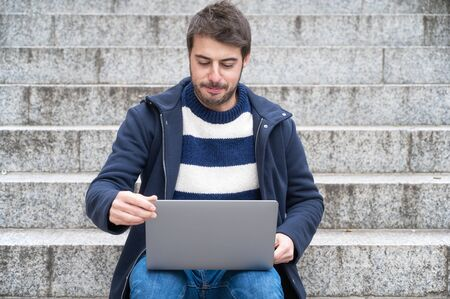 Handsome hipster modern businessman, using laptop in the city, with positive expression. Stock fotó