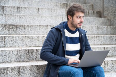 Handsome hipster modern businessman, using laptop in the city, with positive expression. Фото со стока