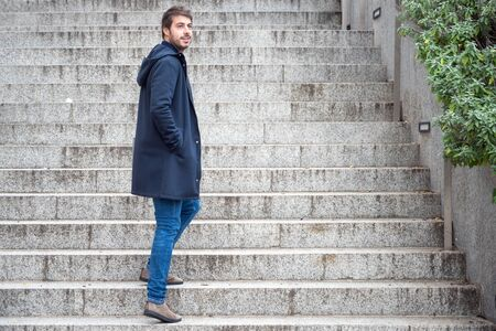 Horizontal portrait of young attractive man standing on steps looking back. Modern and stylish guy holds Laptop hands. Фото со стока