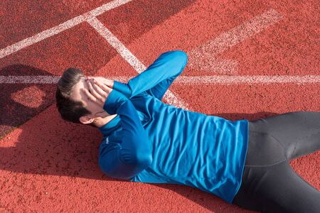 Athlete young man tired, lying on running track. Stock Photo