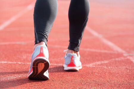Persona atletica sulla pista da corsa che si prepara per iniziare a correre, vista posteriore. Archivio Fotografico