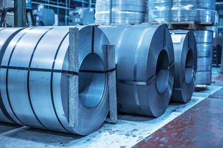 Industrial background. Big size steel coil stored inside industrial warehouse, blue toned image.