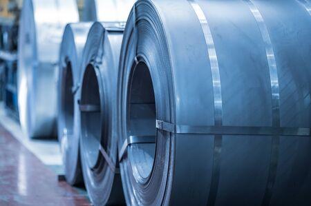 Fondo industrial. Bobina de acero de gran tamaño almacenada dentro de la nave industrial, imagen en tonos azules.