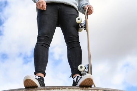 Close up of unrecognizable young man holding longboard or skateboard in the park. Zdjęcie Seryjne