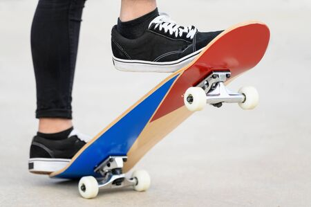 Close up view of teens feet on a skateboard ready to start a ride over the half pipe.