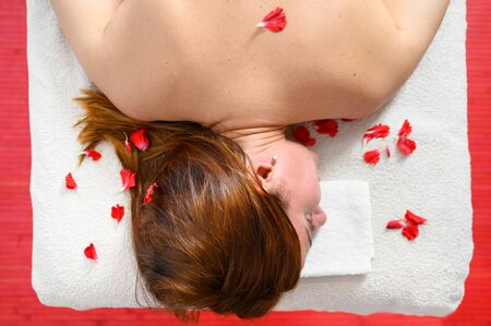 Relaxing woman in a spa with petal of flowers on her back, Beautiful woman relaxed in spa salon, body care, Spa body treatment.