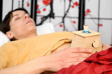 Alternative therapist applying moxibustion a traditional chinese medicine method. Stock Photo