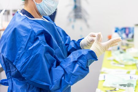 Surgeon putting on sterile gloves in an operating room. Foto de archivo
