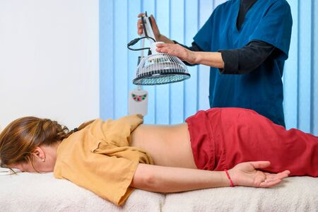 Therapist doing healing infrared treatment on woman back . Alternative medicine, physiotherapy, pain relief concept.