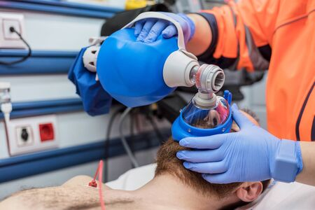 Covid-19 respiratory insufficiency. Urgency doctor using mask Ambu bag on a patient with pneumonia due to Coronavirus infection, for artificial ventilation.