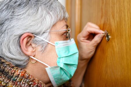 Covid-19 concept. Stay at home. Self-isolation to prevent the coronavirus pandemic. Senior woman in protective green mask looks through the peephole.