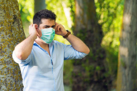 Young man standing in the park removing protective face mask celebrating victory over coronavirus outside in open air. End of quarantine. Remove mask. Outdoor. Freedom. Covid-19. Pandemic crisis end.