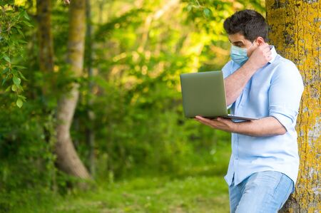 Handsome young man wearing face mask, standing in the park working using his laptop.
