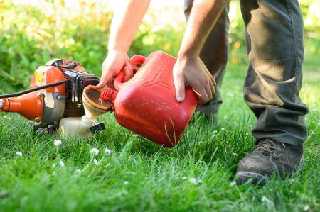 Gärtner tanken Freischneider hautnah. Wartung von Gartengeräten. Rasenpflege mit Freischneider.