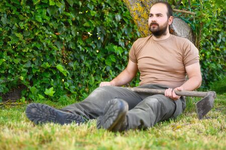 An adult male farmer with a hoe resting in the the farm. Archivio Fotografico
