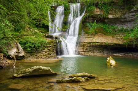 Idyllic rain forest waterfall, stream flowing in the lush green forest.