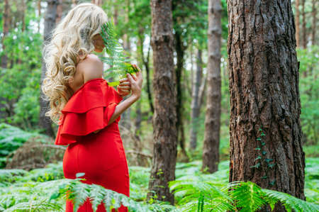Woman in red dress holds fern green leaf.