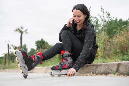 Happy Woman on roller skating pause, sitting on the street and using mobile phone. Pretty, Urban Girl talking on the Phone, wearing Roller Skates. Modern Girl in the City Stock Photo - 151077670