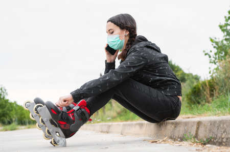 Woman in protective face mask on roller skating pause, sitting on the street and using mobile phone during coronavirus pandemic outbreak. Urban Girl talking on the Phone, wearing Roller Skates. Stock Photo - 151077680