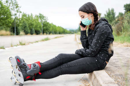 Woman in protective face mask on roller skating pause, sitting on the street and using mobile phone during coronavirus pandemic outbreak. Urban Girl talking on the Phone, wearing Roller Skates. Stock Photo - 151077729
