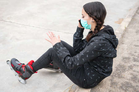 Woman in protective face mask on roller skating pause, sitting on the street and using mobile phone during coronavirus pandemic outbreak. Urban Girl talking on the Phone, wearing Roller Skates.