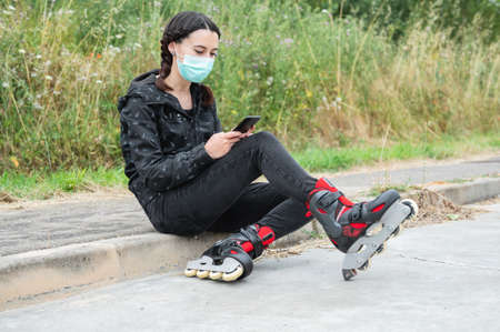 Woman in protective face mask, on roller skating pause, sitting on the street and using mobile phone during coronavirus pandemic outbreak. Urban Girl using phone, wearing Roller Skates.