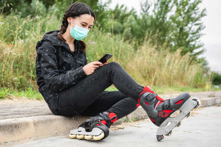 Woman in protective face mask, on roller skating pause, sitting on the street and using mobile phone during coronavirus pandemic outbreak. Urban Girl using phone, wearing Roller Skates. Stock Photo - 151077738