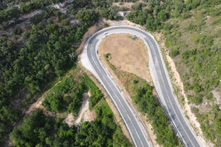 Aerial view of winding road in high mountain pass trough green pine woods. High quality photo Stock Photo - 151305019