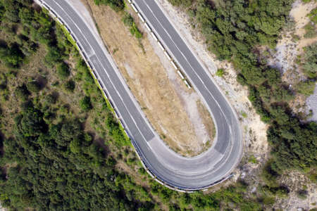 Aerial view of winding road in high mountain pass trough green pine woods. High quality photo