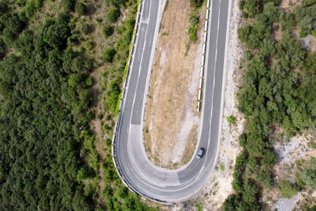 Aerial view of winding road in high mountain pass trough green pine woods. High quality photo Stock Photo - 151305023