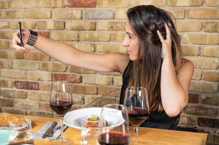 Beautiful Young woman is taking a selfie photograph while eating in restaurant. Stock Photo