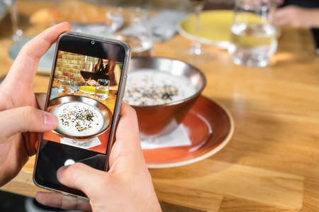 Man hand with smartphone photographing food at restaurant or cafe
