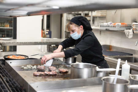 Woman Chef in protective face mask prepare food in the kitchen of a restaurant or hotel. Coronavirus prevention concept.