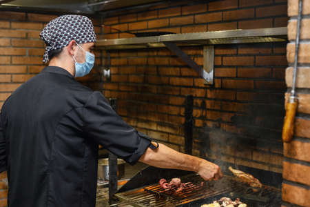 Chef grilling steaks in commercial kitchen Stock Photo