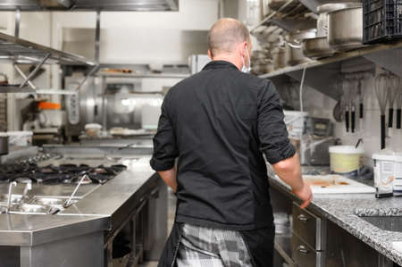 Chef in uniform cooking in a commercial kitchen. Male cook wearing apron standing by kitchen counter preparing food. Stock Photo
