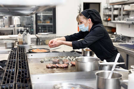 Chef in uniform cooking in a commercial kitchen. Female cook wearing apron standing by kitchen counter preparing food.