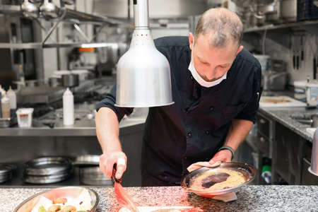 Chef in uniform cooking in a commercial kitchen. Male cook standing by kitchen counter preparing food.