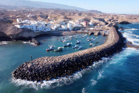 Aerial view of a little fishing town with some colorful boats in Tajao, Tenerife, Canary Islands.