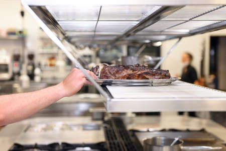 Commercial kitchen background.Chef hand with plate of grilled meat ready to serve . Stock Photo