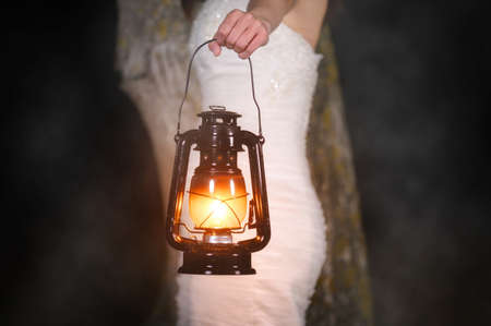 Unrecognizable Woman with Vintage Lantern Outside at Night. Young woman in white long dress walking in night wood. Stock Photo