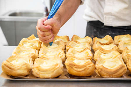 Pastry chef decorates biscuit tartlet with cream from pastry bag close-up