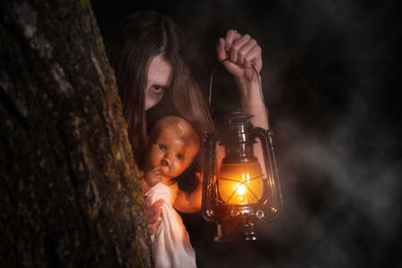 Scary woman with a lantern in night scene - Spooky image of a scary woman with dark eyes and appearance of a witch, in a white dress, holding a lit lantern and a frightening doll, in a dark night atmosphere .